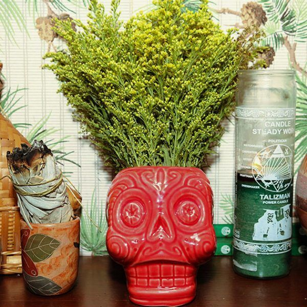 Skull-shaped vase on a shelf with other design objects