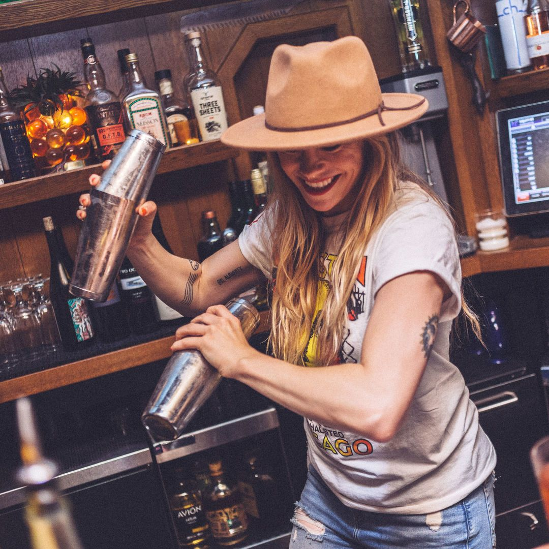Barwoman with a cap making cocktails