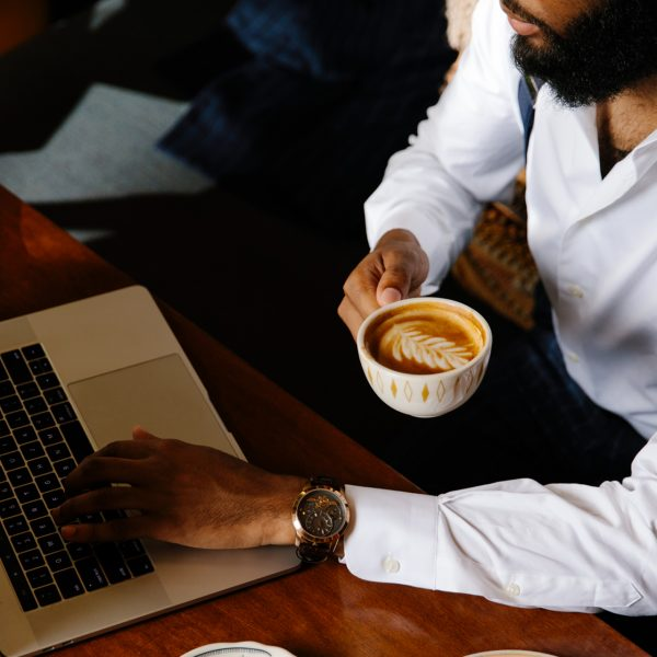 A man working with the computer and drinking a coffee