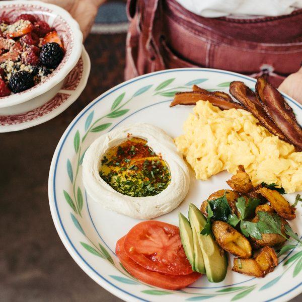 Waitress bringing a fruit salad and an english breakfast