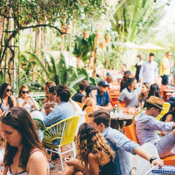 Backyard with people sitting and talking at Freehand Hotel Miami