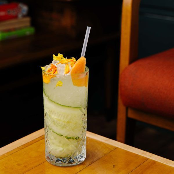 Drink in a cocktail glass with a slice of cucumber and some topping flowers