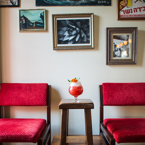 Room corner with two red chairs, some pictures hung on the wall and a stool with a cocktail glass on it