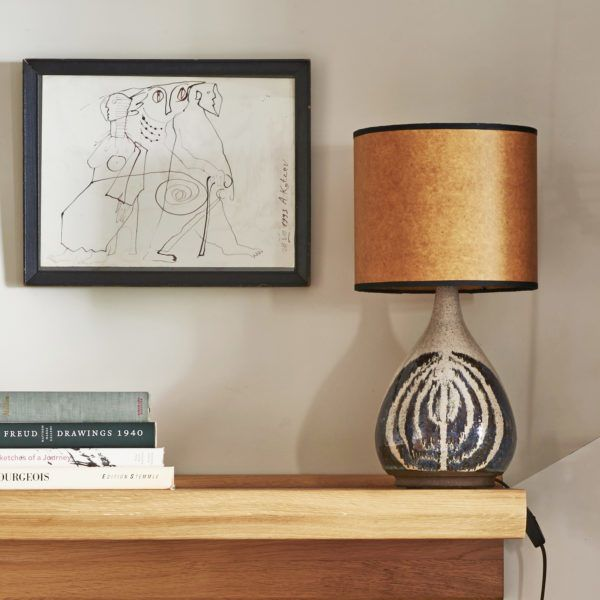 Design corner with a shelf, some books a lamp and a frame on the wall