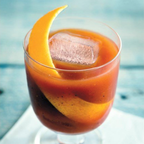 Red cocktail with orange zest