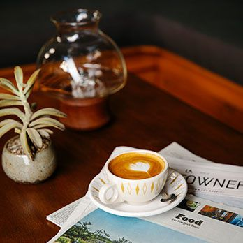 Table with a cup of cappuccino and some newspapers on it