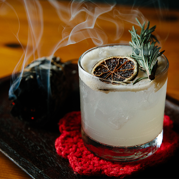 Cocktail with some herbs burning on a side